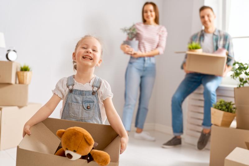 Familia joven feliz se muda a nuevo apartamento. Padres e hija con cajas.